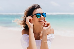 Wonderful woman in white attire and sparkle glasses posing with happy face expression in hot summer day. Pleasant caucasian girl standing near ocean on sky background..