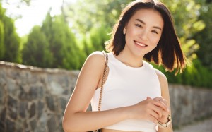 Image of modern asian woman standing in park and smiling. Stylish asia girl looking at camera with happy face, walking in city